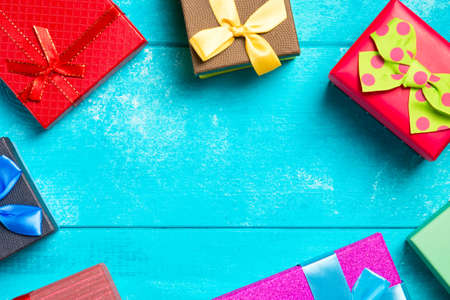 Colorful gift boxes with ribbons on nice blue wooden background. Copy space. Christmas or birthday celebration holiday theme Stock Photo
