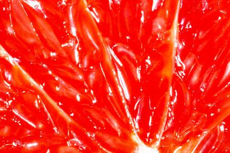 Closeup texture of a grapefruit slice. Fruit natural macro background.