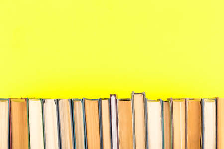 Books in a row against yellow background. Free space for your text.