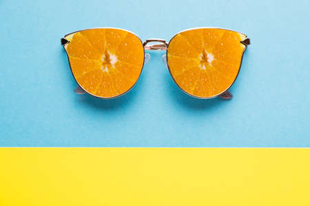 Summer vacation concept. Sunglasses with orange fruits on blue yellow background