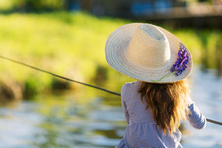 Cute little child girl in straw hat with lupine flower fishing on a lake. Family leisure activity.