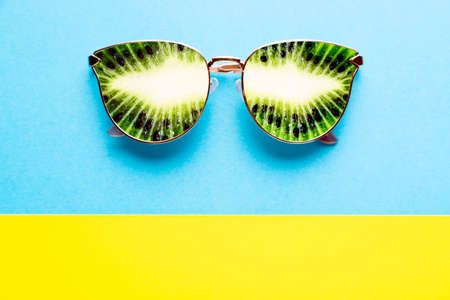 Summer vacation concept. Sunglasses with kiwi tropical fruits on blue yellow background