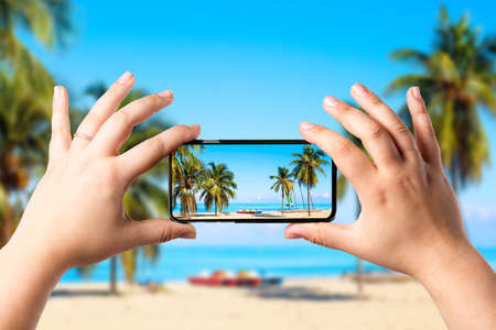 Female hands holding mobile smart phone and making photo of amazing beach with palms and ocean. Vacation and relaxation concept