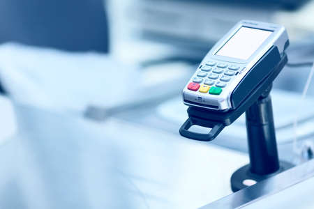 Credit card POS terminal at the checkout in a store. Retail business equipment and finance concept. Toned.