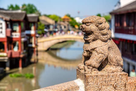 Qibao Old Town in Shanghai, China. Stone statue on brick bridge over the river in Qibao