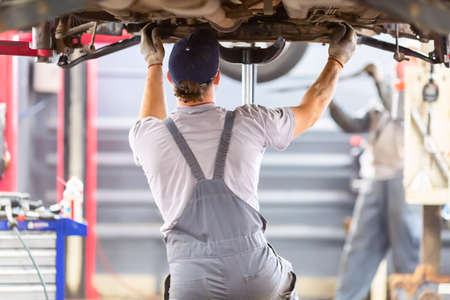 Car repair service. Mechanic working with a car in mechanical workshop.