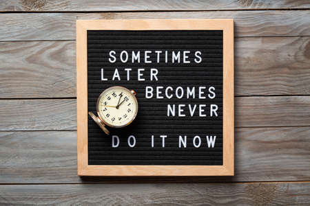 Inspirational motivational quote Sometimes later becomes never. Do it now words on a letter board on wooden background near vintage alarm clock. Success and motivation concept Stock Photo