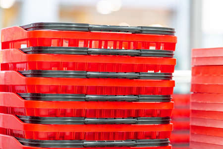 Red plastic shopping baskets in the supermarket store Stock Photo