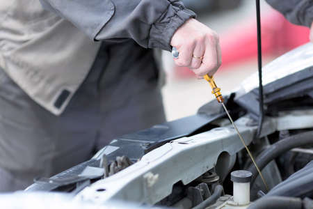 Car repair service. Mechanic checking the oil level in car engine