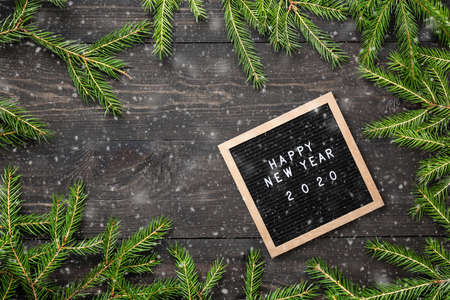 Christmas or new year frame for your project. Happy new year 2020 words on a letter board with Christmas fir tree branches and snow on a dark wooden board