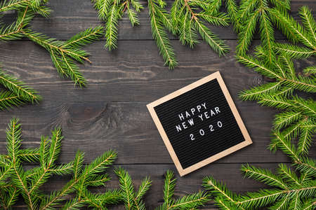Christmas or new year frame for your project. Happy new year 2020 words on a letter board with Christmas fir tree branches on a dark wooden board