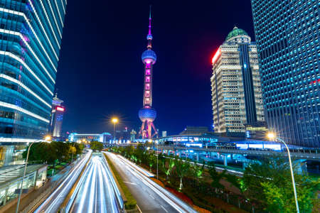 Street traffic at night in Shanghai, China. Office skyscraper buildings and television tower with car light trails