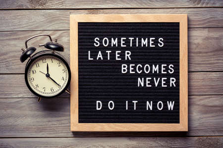 Inspirational motivational quote Sometimes later becomes never. Do it now words on a letter board on wooden background near vintage alarm clock. Success and motivation concept