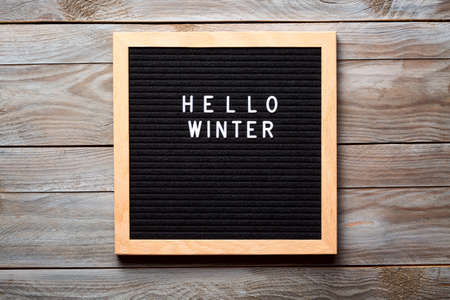 Christmas or new year frame or mockup for your project. Seasonal frame. Hello Winter words on a letter board on wooden background. Stock Photo