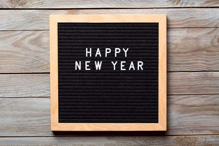 Christmas or new year frame or mockup for your project. Happy new year words on a letter board on wooden background.