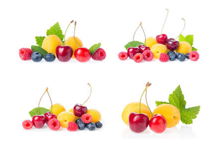 Healthy fresh fruits collage set group mix. Composition of ripe red sweet cherry with horns, raspberries, apricots and blueberries with leaves isolated on white background.
