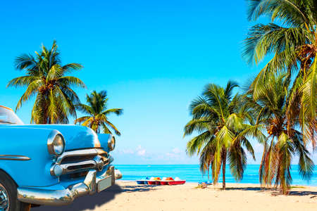 The tropical beach of Varadero in Cuba with american classic car, sailboats and palm trees on a summer day with turquoise water. Vacation background