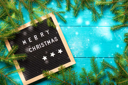 Christmas background. Christmas fir tree branches with snow on blue rustic wooden board near letter board with words Merry Christmas