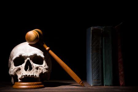 Legal law, justice and murderment concept. Wooden judge gavel hammer on human skull near books against black background Stock Photo