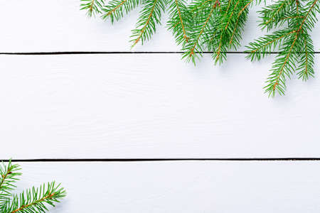 Christmas background. Christmas fir tree branches on white rustic wooden board with copy space.