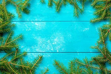 Christmas background. Christmas fir tree branches on blue rustic wooden board with copy space.