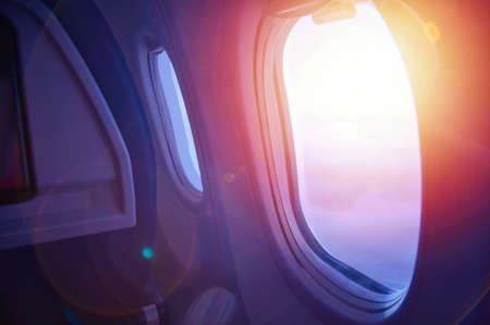 Travel concept. Sunset through an airplane window. Plane interior Stock Photo