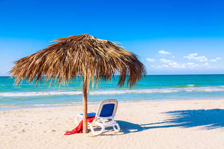 A sun lounger under an umbrella on the sandy beach by the sea and sky. Vacation background. Idyllic beach landscape Stock Photo