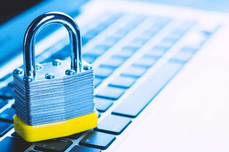 Vorhängeschloss am Laptop. Informationssicherheitskonzept für den Datenschutz im Internet. Antivirus- und Malware-Abwehr. Blau getönt. Standard-Bild