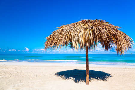 Straw umbrella on a beach. Vacation background. Idyllic beach landscape