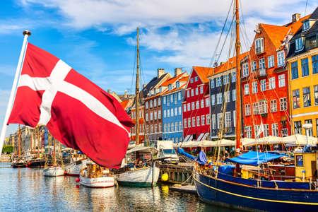 Kultowy widok Kopenhagi. Słynny stary port Nyhavn w centrum Kopenhagi w letni słoneczny dzień z flagą Danii na pierwszym planie.