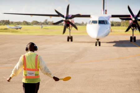 Airport worker signaling and directing a plane on the airport runway. Aviation concept Reklamní fotografie
