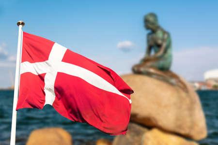 Posąg Małej Syrenki w Kopenhadze z flagą Danii. Bardzo popularna atrakcja turystyczna