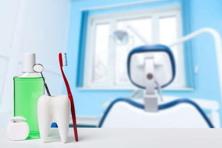 Dental health and teethcare concept. Dental mirror in white tooth model near mouthwash, toothbrush and dental floss against dental office and chair background.
