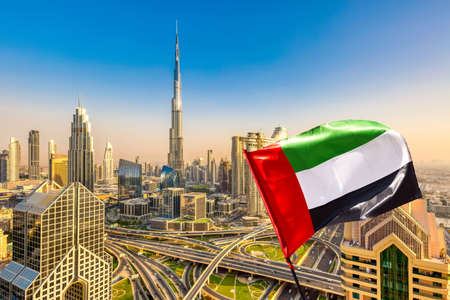 Amazing Dubai skyline cityscape with modern skyscrapers and UAE flag. Downtown of Dubai at sunny day, United Arab Emirates Imagens