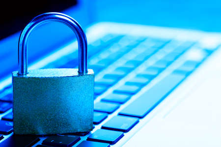 Padlock on laptop. Internet data privacy information security concept. Antivirus and malware defense. Blue toned.