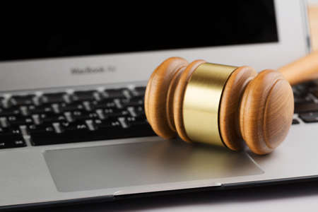Online auction or cyber law concept. Judge court gavel on a modern laptop computer. Banco de Imagens