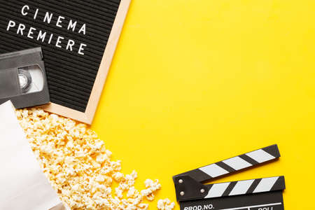Cinema concept. Popcorn in a box, movie clapper, VHS video cassette tape and letter board with words cinema premiere on yellow background. Free space