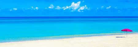 Pink beach umbrella parasol on the tropical beach. Vacation background. Idyllic beach landscape. Wide banner format.