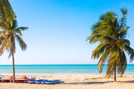 The tropical beach of Varadero in Cuba with sailboats and palm trees on a summer day with turquoise water. Vacation background Imagens