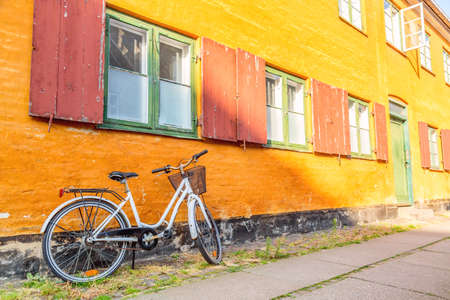 Picturesque of Copenhagen. Old yellow house of Nyboder district with bike. Old Medieval district in Copenhagen, Denmark.