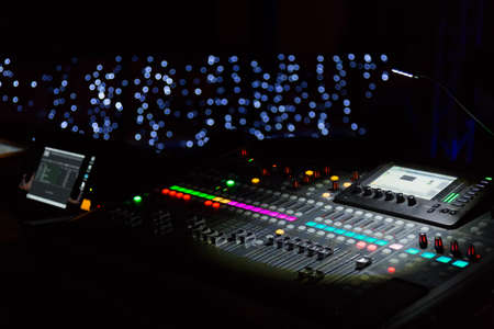 Audio sound mixer console with buttons and sliders with lights at the concert. Selective focus.