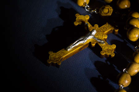 Jesus Christ catholic crucifix and wooden rosary beads on a bible under beam of light.
