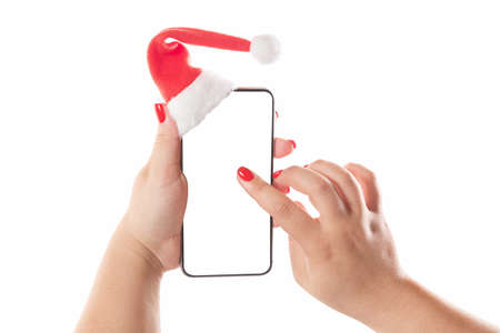 Female hands holding mobile smart phone with santa hat isolated on white background. Blank white screen. Concept of Christmas congratulation. Imagens