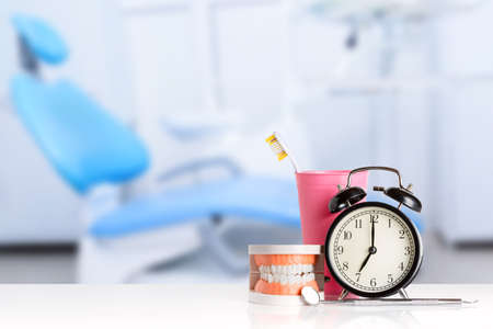 Dental mirror and dental explorer instrument near human jaw, alarm clock and toothbrush in pink glass against dental office chair background. Brush teeth concept 免版税图像