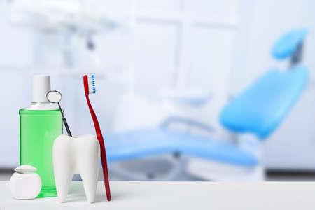 Zahngesundheits- und Zahnpflegekonzept. Zahnspiegel im weißen Zahnmodell in der Nähe von Mundwasser, Zahnbürste und Zahnseide vor Zahnarztpraxis und Stuhlhintergrund. Standard-Bild