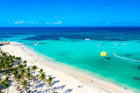 Aerial drone view of beautiful caribbean tropical beach with straw umbrellas, palms and boats. Bavaro, Punta Cana, Dominican Republic. Vacation background