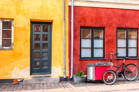 Old red and yellow houses in the center of Copenhagen with typical bicycle. Old Medieval district in Copenhagen, Denmark. Stockfoto - 147337223