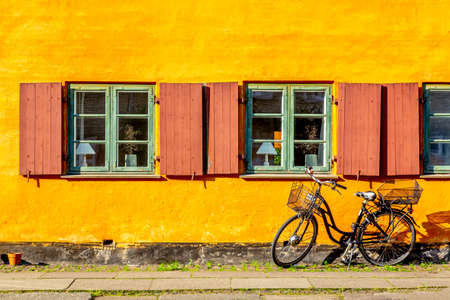 Old yellow house of Nyboder district with a bicycle. Old Medieval district in Copenhagen, Denmark. Banque d'images