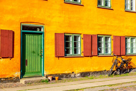 Old yellow house of Nyboder district with a bicycle. Old Medieval district in Copenhagen, Denmark.