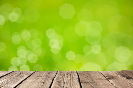 Empty light wood table or rustic wooden planks against defocused blurred nature green background with soft bokeh lights. Space for your background placement or products 版權商用圖片